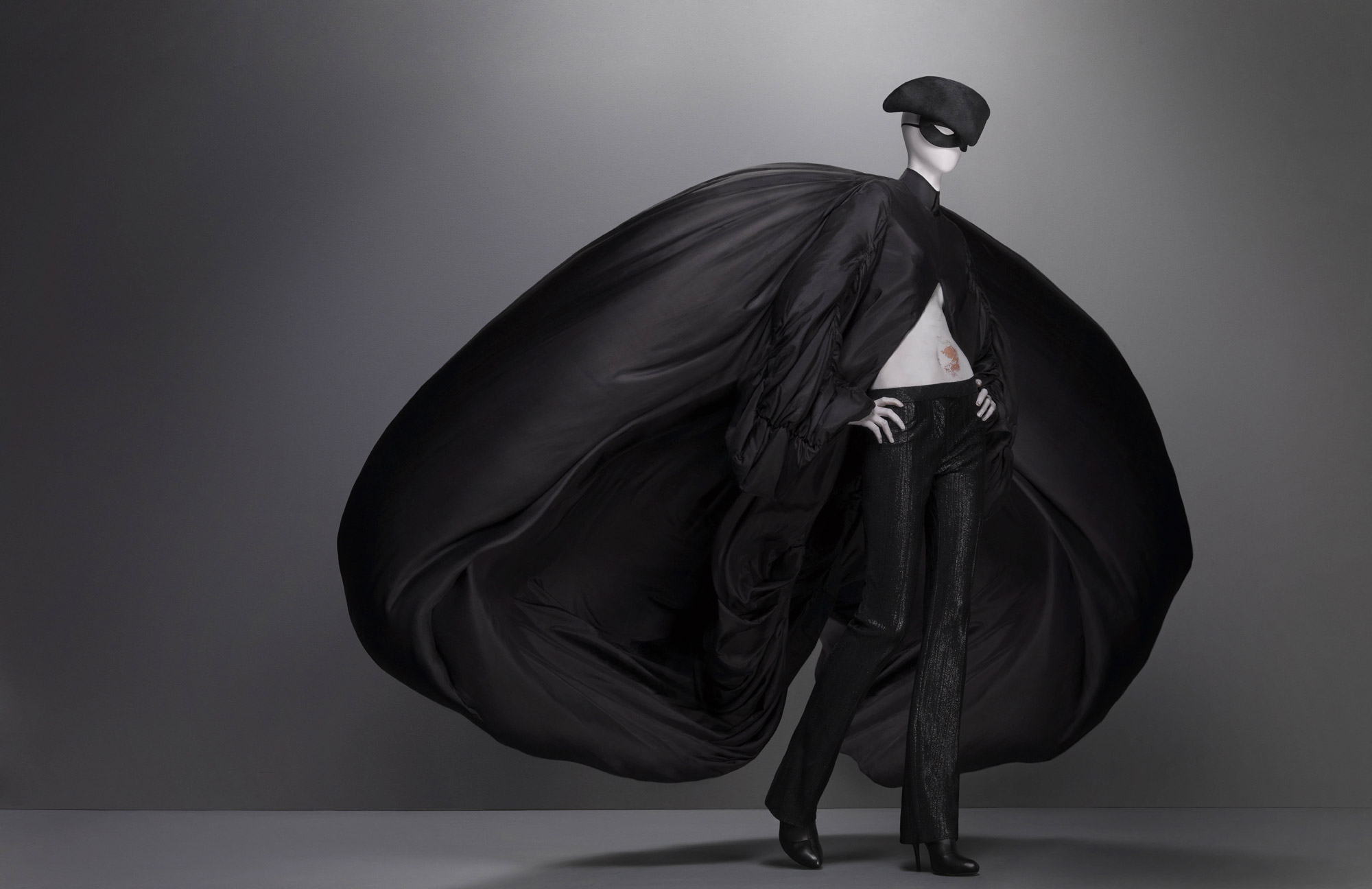 Supercalifragilisticexpialidocious, autumn/winter 2002–3 Coat of black parachute silk; trouser of black synthetic; hat of black silk satin Hat by Philip Treacy for Alexander McQueen